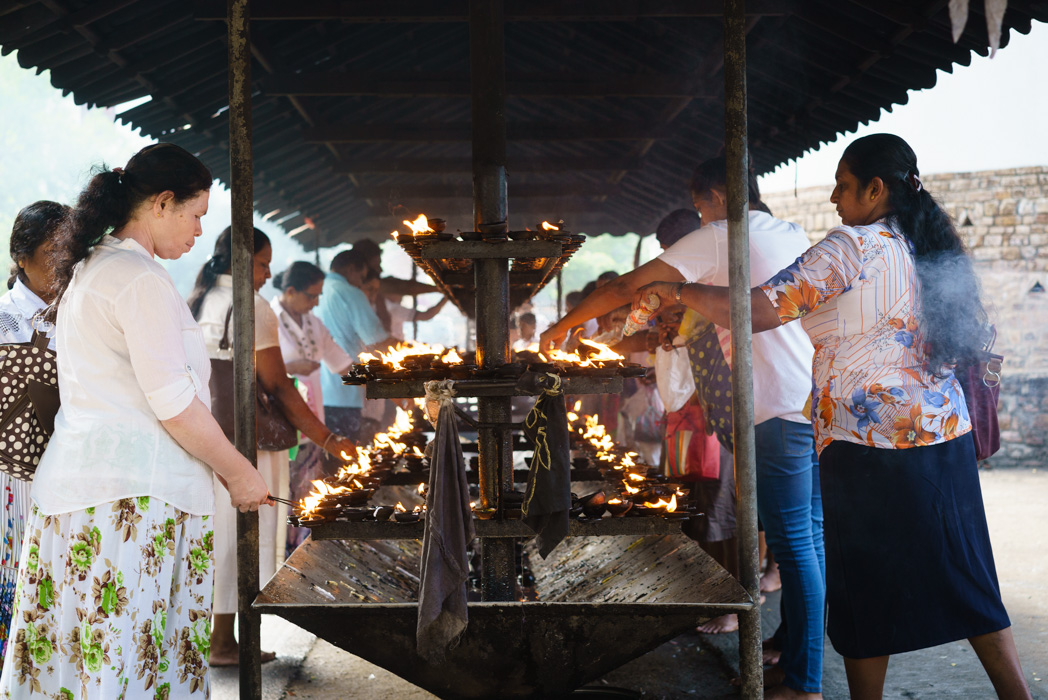 Lighting a flame and praying at the temple of the tooth